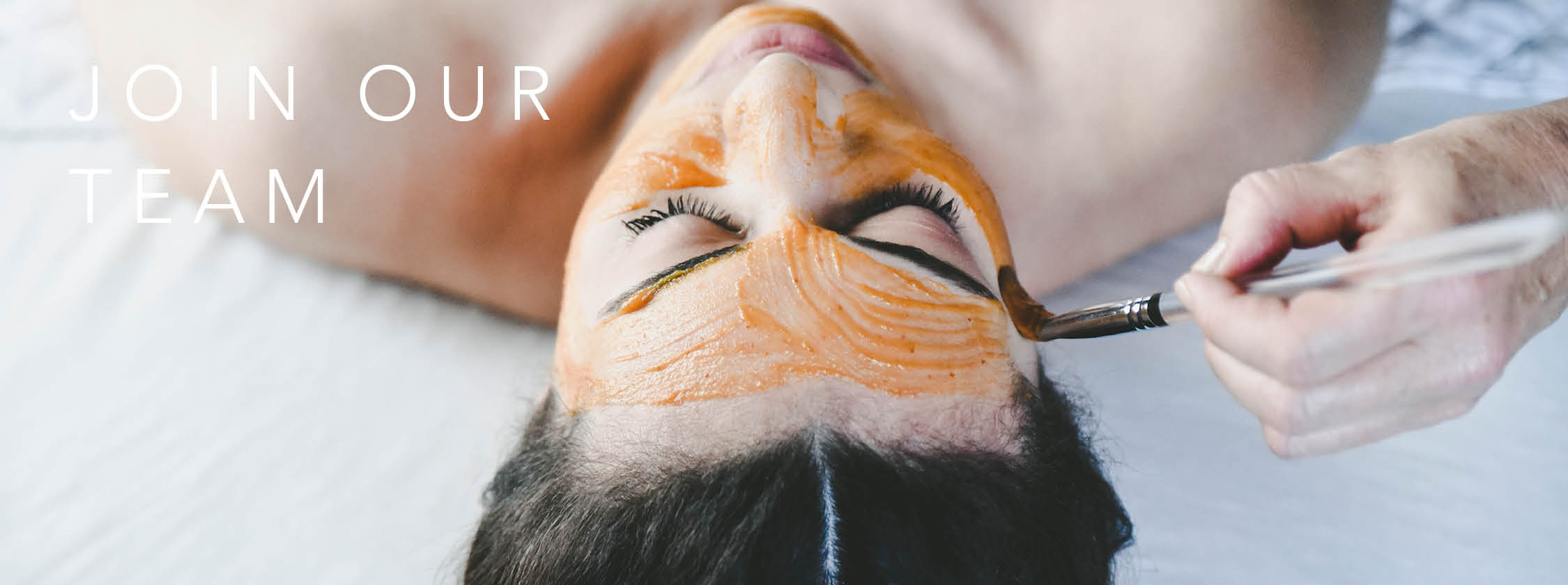 A woman lays on her back, receiving a facial treatment