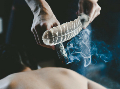 A man's hands hold smoking herbs and a feather are are used during a wellness treatment